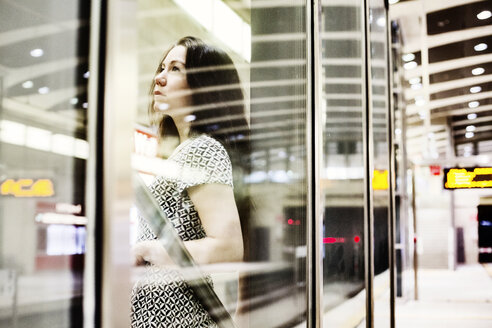 Portrait of young woman waiting behind glass wall on underground station platform - JATF00997