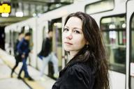 Germany, Cologne, portrait of young woman at underground station platform - JATF01000