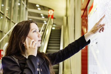 Germany, Cologne, young woman on the phone looking at city map in underground station - JATF01003