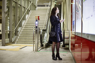 Germany, Cologne, young woman with cell phone looking at city map in underground station - JATF01006