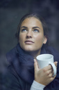 Portrait of young woman with coffee mug looking out of window - PNEF00397