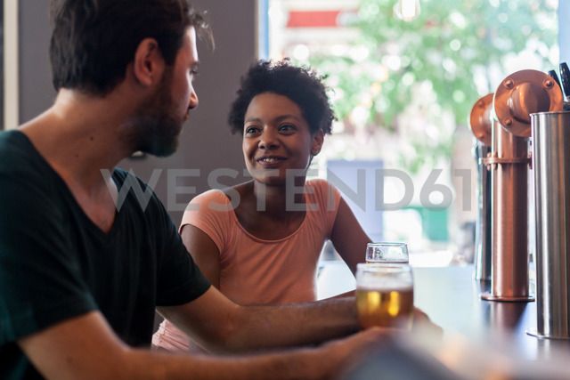 Couple talking and drinking beer in a bar - LFEF00003