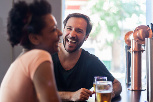 Laughing couple talking and drinking beer in a bar - LFEF00006