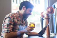 Smiling man with beer glass using tablet in a bar - LFEF00009