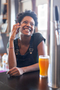 Smiling woman on cell phone with beer glass in a bar - LFEF00012