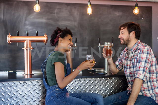 Couple talking and drinking beer in a bar - LFEF00015