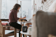 Woman sitting in studio taking notes - OCAF00028
