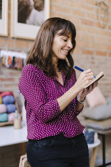 Smiling woman in knitting studio taking notes - OCAF00031
