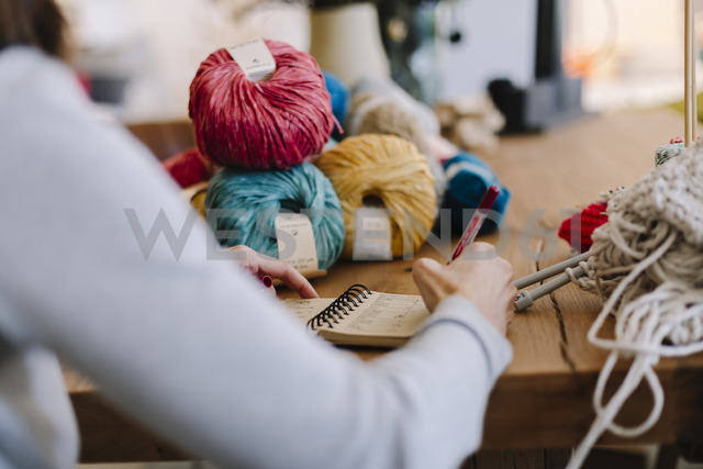 Close-up of woman taking notes on table with knitting - OCAF00040