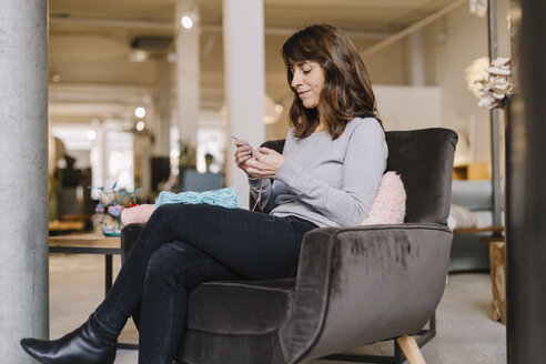 Woman sitting in armchair knitting - OCAF00043
