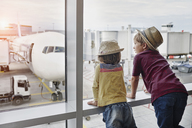 Two children wearing straw hats looking through window to airplane on the apron - RORF01059