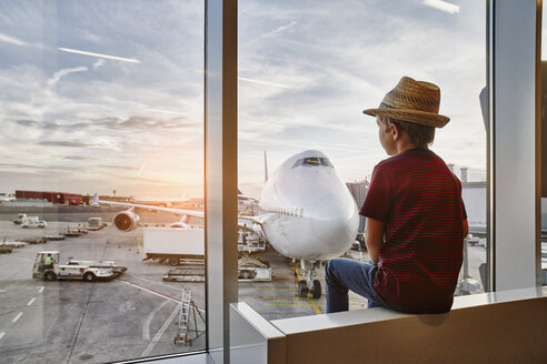 Boy wearing straw hat looking through window to airplane on the apron - RORF01065