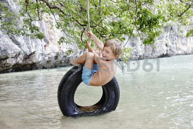 Thailand, Ko Yao Noi, Phang Nga Bay, happy boy swinging on tire above the sea - RORF01074