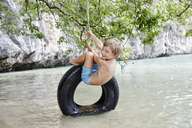 Thailand, Ko Yao Noi, Phang Nga Bay, happy boy swinging on tire above the sea - RORF01074