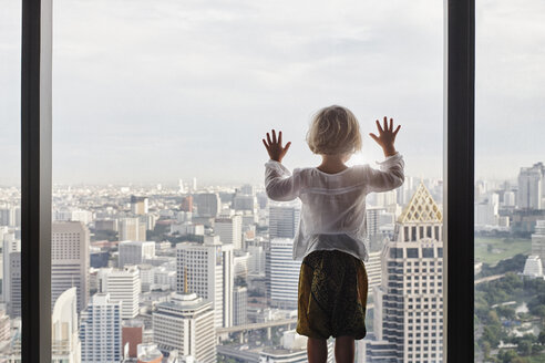 Thailand, Bangkok, little girl looking through window at cityscape - RORF01080