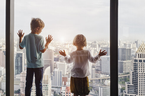 Thailand, Bangkok, boy and little girl looking through window at cityscape - RORF01083