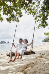 Thailand, Ko Yao Noi, happy boy and little girl on a swing on the beach - RORF01086