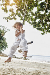 Thailand, Phi Phi Islands, Ko Phi Phi, smiling little girl on a rope swing on the beach - RORF01104