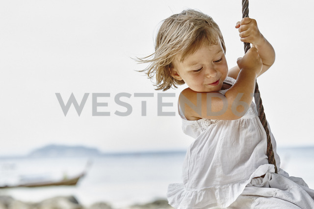 Thailand, Phi Phi Islands, Ko Phi Phi, happy little girl on a rope swing on the beach - RORF01107