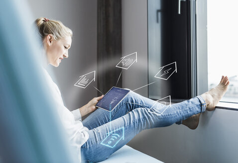 Woman sitting in office, using digital tablet to remote-control his smart home - UUF12532