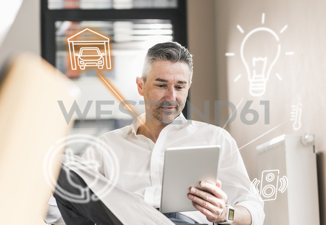 Man sitting in office, using digital tablet to remote-control his smart home - UUF12535