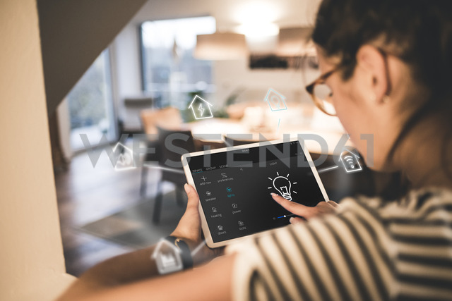 Woman sitting at home, using digital tablet to remote-control his smart home - UUF12538