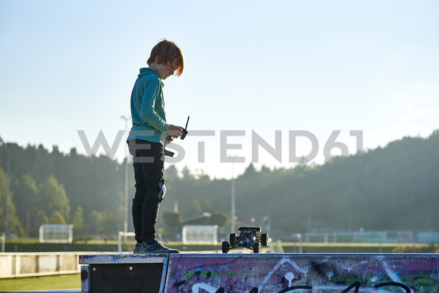 Boy standing on wall playing with remote-controlled car - JEDF00297