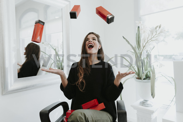 Excited young woman juggling with cosmetics in beauty salon - OCAF00054
