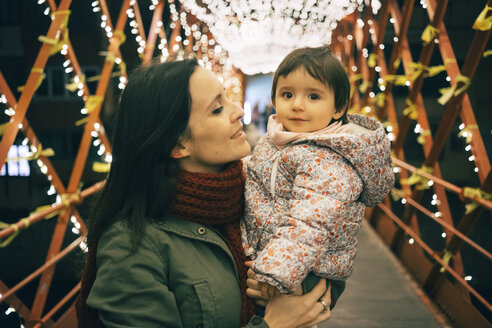 Mother and baby girl on bridge with lights at Christmas - GEMF01851