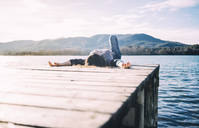 Woman resting on a wooden jetty at a lake - GEMF01854