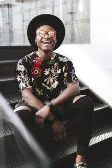 Portrait of laughing man wearing hat, sunglasses and black t-shirt with floral design sitting on stairs - OCAF00059
