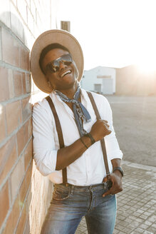 Portrait of laughing young man wearing hat and sunglasses - OCAF00068