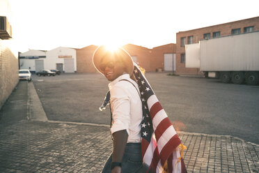 Laughing young man with American flag at backlight - OCAF00071