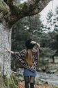 Back view of young woman wearing hat and poncho in autumnal forest - OCAF00074
