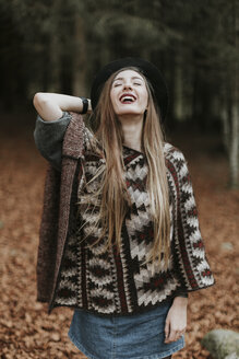 Portrait of laughing of young woman wearing hat and poncho in autumnal forest - OCAF00077