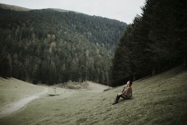 Young woman sitting on a meadow near forest edge looking up - OCAF00080