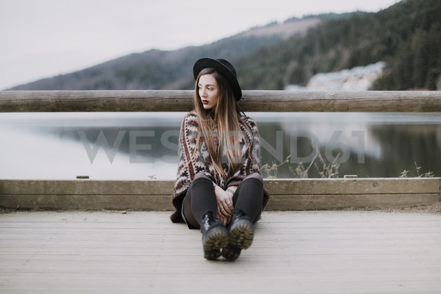 Portrait of fashionable young woman wearing hat and poncho sitting on wood bridge - OCAF00083