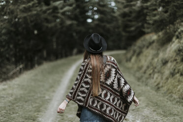 Back view of fashionable young woman wearing hat and poncho in nature - OCAF00089