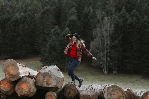 Young woman balancing on logs - OCAF00092