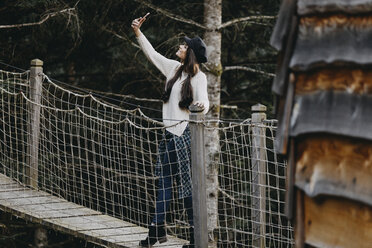 Young woman on a suspension bridge at tree house in forest taking a selfie - OCAF00096
