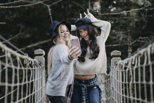 Two happy young women on a suspension bridge taking a selfie - OCAF00099