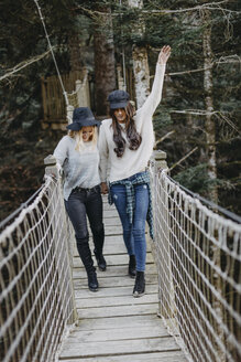 Two happy young women walking on a suspension together - OCAF00102