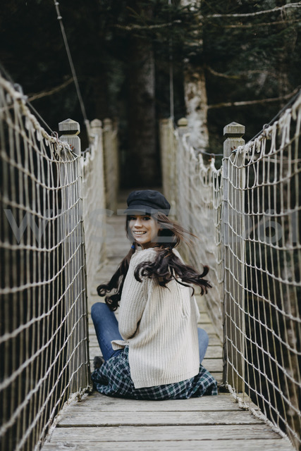 Portrait of smiling young woman sitting on a suspension bridge - OCAF00105