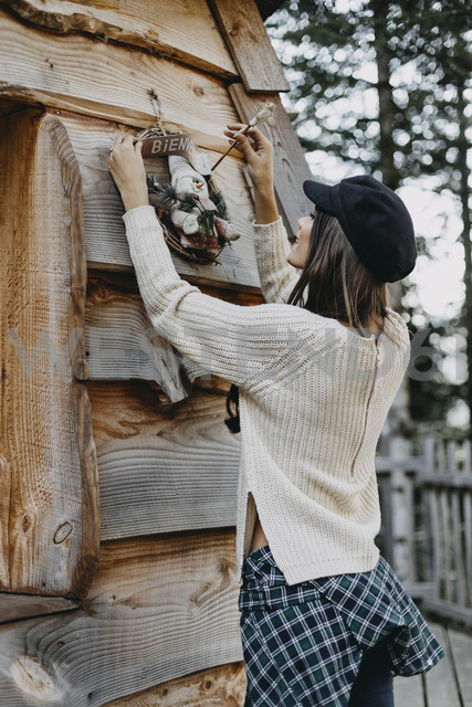 Young woman decorating wooden house with Christmas decoration - OCAF00108