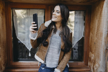 Happy young woman at the window of a wooden house taking a selfie - OCAF00114