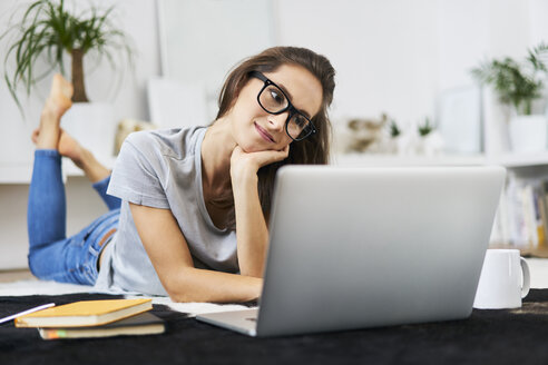 Young woman at home lying on the floor using laptop - BSZF00143