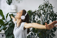 Happy young woman with oustretched arms listening to music at indoor plant - BSZF00158