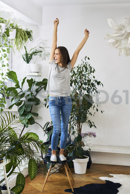 Young woman standing on chair in a room cheering - BSZF00161