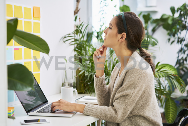 Young woman with laptop on desk looking at adhesive notes on the wall - BSZF00164