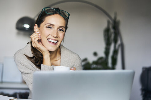 Portrait of happy young woman at home with laptop - BSZF00167